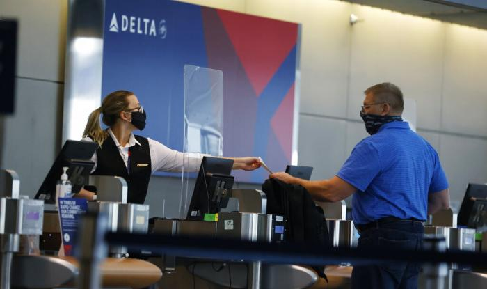 a ticketing agent for Delta Airlines hands a boarding pass to a passenger as he checks in for a flight in the main terminal of Denver International Airport in Denver.