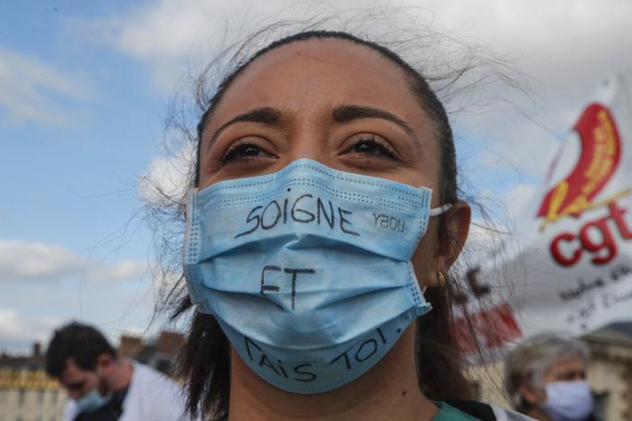 """A medical worker wears as mask that reads """"heal and shut up,"""" as she demonstrates to demand better salaries and working conditions in Paris, Thursday, Oct. 15, 2020."""