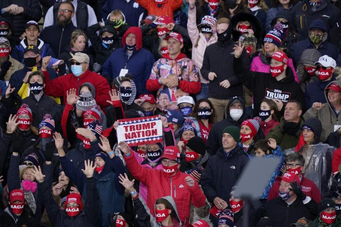 Supporters of President Donald Trump cheer as he speaks at a campaign rally, Saturday, Oct. 17, 2020, in Norton Shores, Mich. (AP Photo/Carlos Osorio)