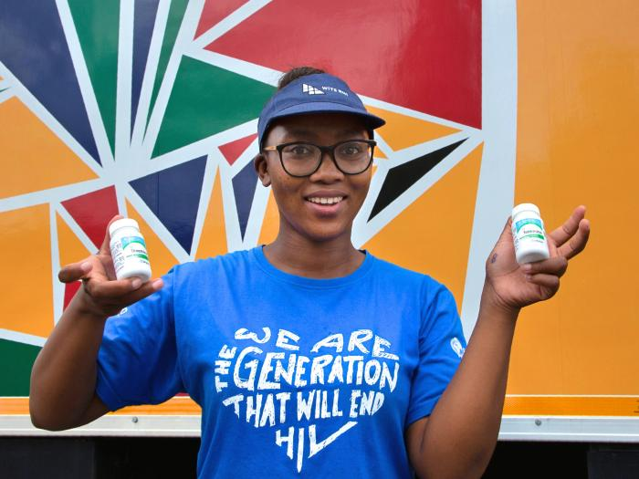 Khanyiswa Kwatsha, who runs a mobile clinic for the Reproductive Health and HIV Institute (RHI) background, shows containers of PrEP medication used in the prevention of HIV infection.
