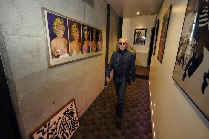 Jed Leiber walks through a hallway with art decorating the walls at home Thursday, Dec. 3, 2020, in Los Angeles. (AP Photo/Marcio Jose Sanchez)