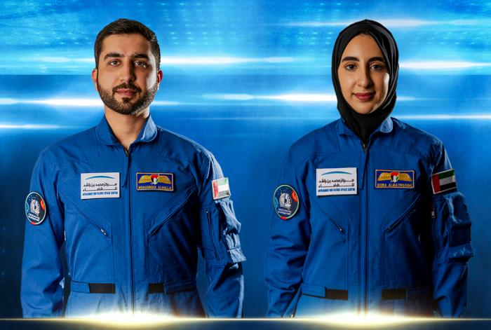 In this undated handout photograph from the United Arab Emirates' state-run WAM news agency, newly named Emirati astronauts Mohammed al-Mulla, left, and Noura al-Matroushi, right, pose for a photo.