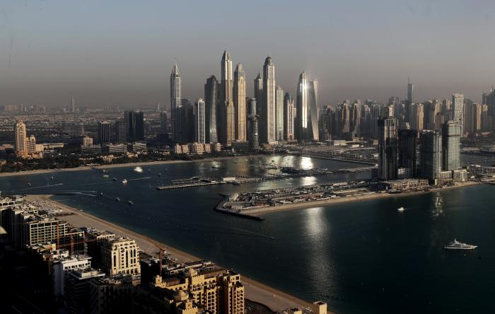 """Luxury towers dominate the skyline in the Marina district, center, and the new Dubai Harbour development, right, are seen from the observation deck of """"The View at The Palm Jumeirah"""" in Dubai."""