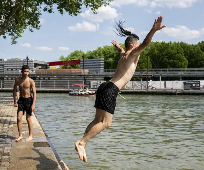 Youths dive in the Canal de l'Ourcq Wednesday, June 16, 2021 in Paris.